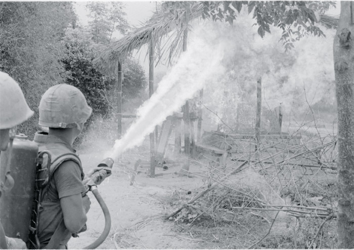 A US Marine torches a Vietnamese home with a flamethrower.