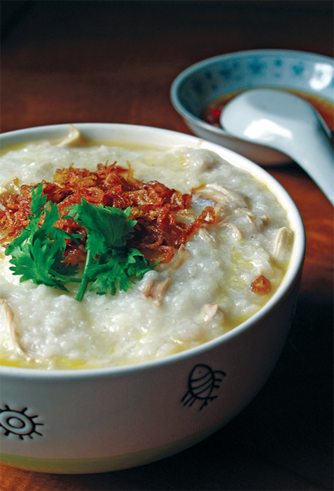 A bowl of chicken congee with egg, fried shallot, and Chinese parsley.