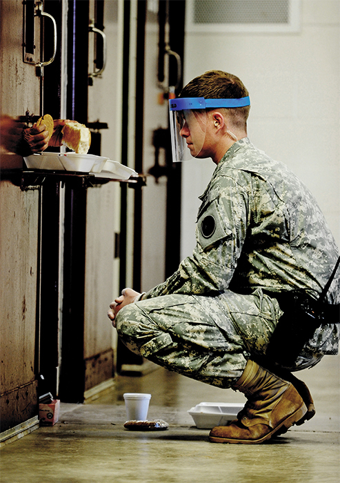 A guard monitoring a detainee eating lunch at the Guantánamo Bay prison camp, 2011.