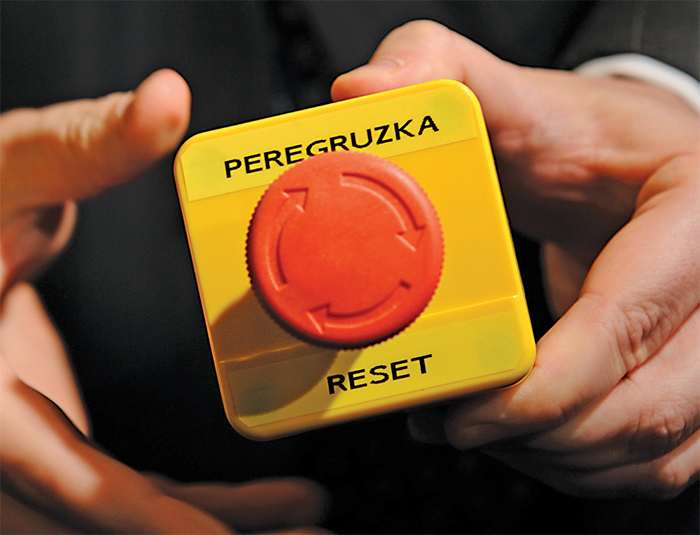 "The ""reset"" button (mistranslated as ""overcharge"") presented by Hillary Clinton to Russian foreign minister Sergey Lavrov, March 6, 2009. Reuters/Fabrice Coffrini/Pool/Alamy"