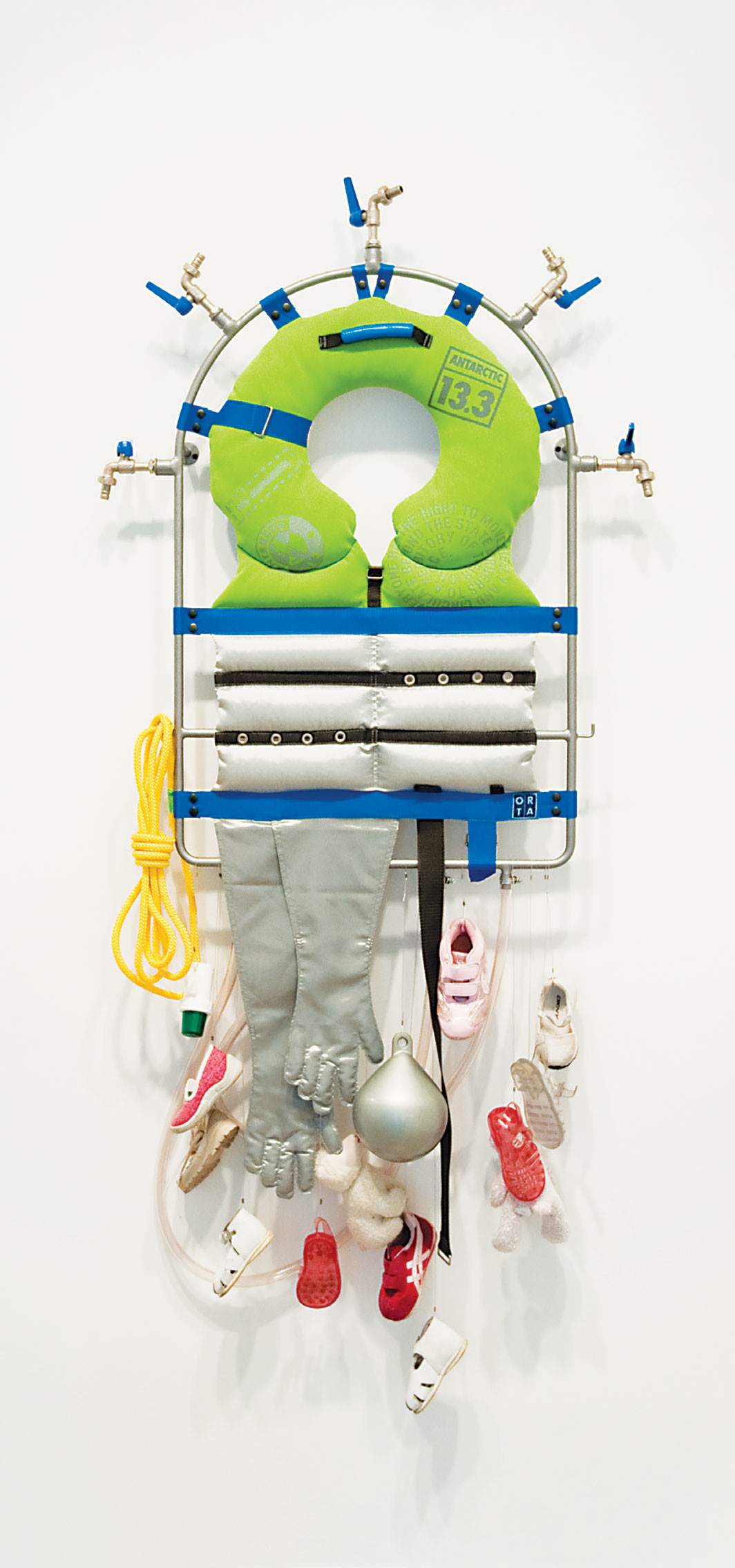 "Lucy and Jorge Orta, Life Line – Survival Kit, 2008, steel frame, piping, taps, textiles, silk screen on fabric, webbing, shoes, float, warning light, rope, 59 × 31 1⁄2 × 5 7⁄8"". Courtesy the artist and Jane Lombard Gallery"